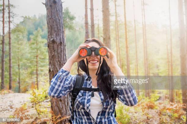 Young female explorer looking through binoculars
