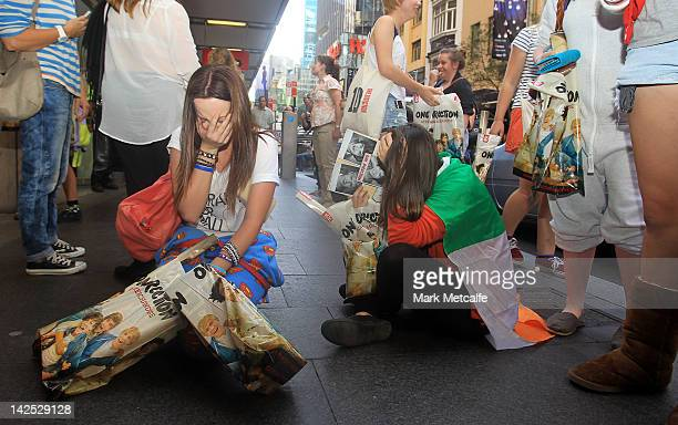 Young female fans are seen crying after purchasing merchandise at the One Direction promotional store opening on Pitt Street on April 7 2012 in...