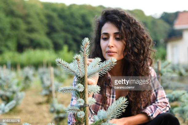 Young female farmer researching plants