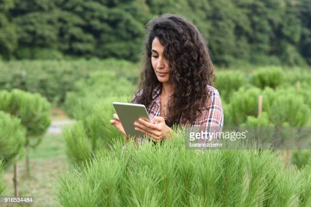 Young female farmer researching plants with digital tablet