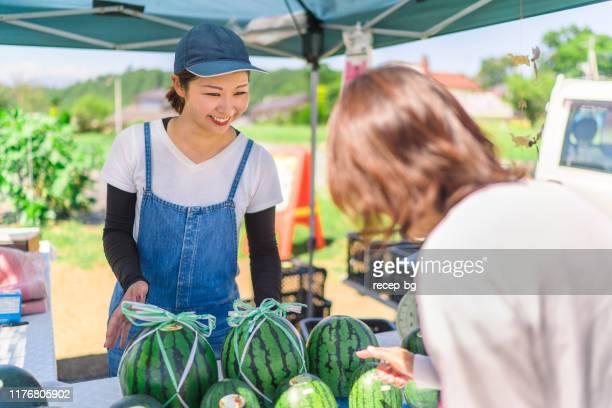 彼女の農家の市場の屋台でスイカを販売する若い女性農家 - ファーマーズマーケット ストックフォトと画像