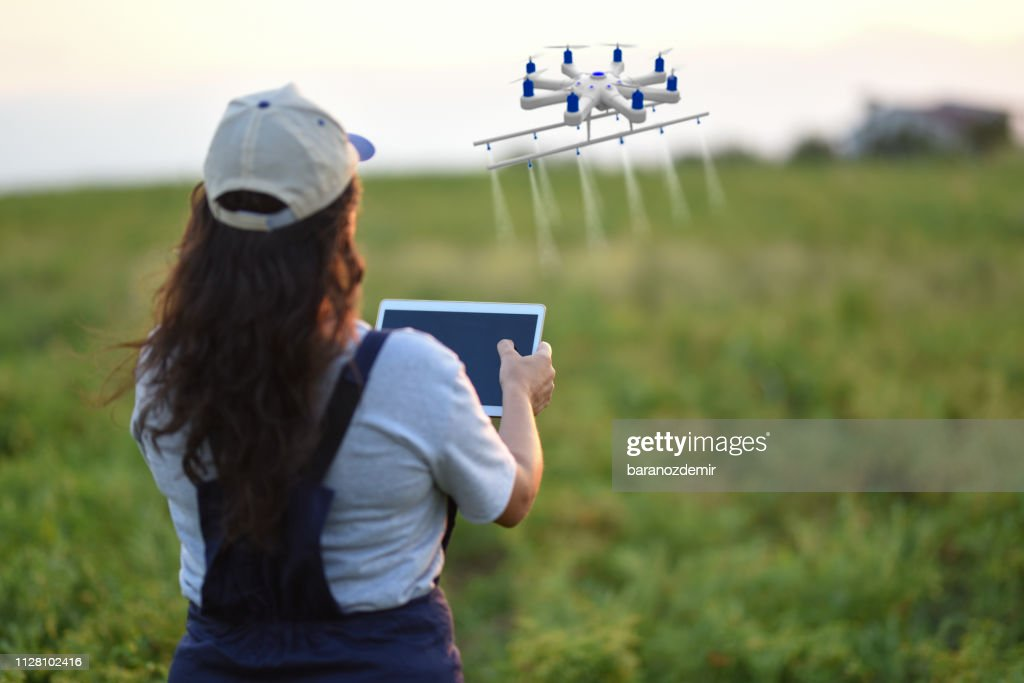 Young Female Farmer Spraying Her Crops Using A Drone Stock