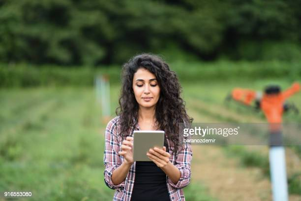 Young female farmer using a digital tablet to control the irrigation system