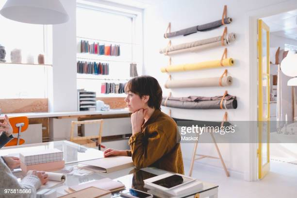 young female fashion designer in discussion with colleagues in workshop - interior designer stock pictures, royalty-free photos & images