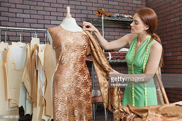 Young female fashion designer matching cloth with fabric draped on tailor's dummy