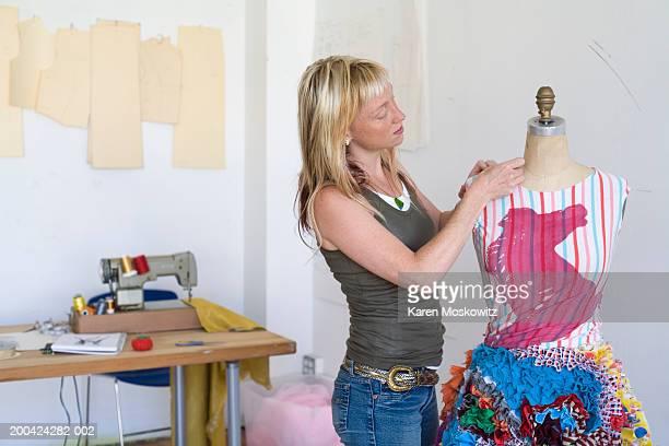 young female fashion designer working on garment on dressmaker's model - top garment stock-fotos und bilder
