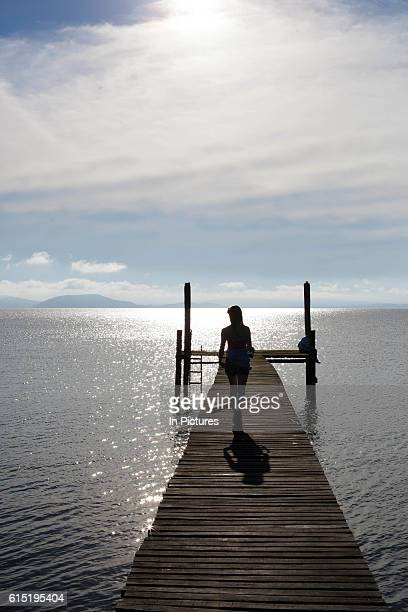 Young female figure silhouette walking towards camera down a Jetty on the banks of a lake at dawn showing vanishing point Working Gaucho Fazenda in...