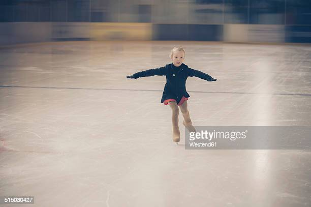 Young female figure skater moving on ice rink at competition