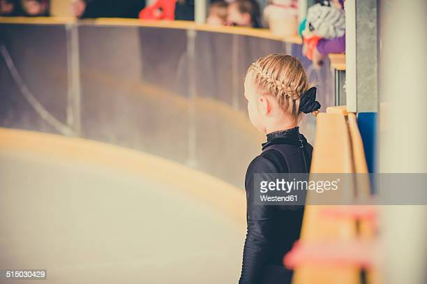 Young female figure skater waiting on ice rink