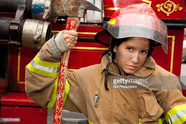 Young Female Firefighter Sitting Next To Firetruck