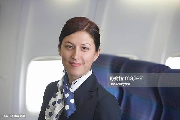 Young female flight attendant aboard empty airplane, portrait