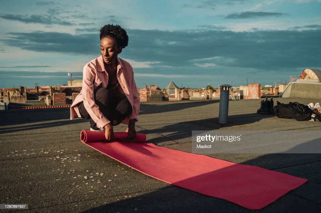 Young female folding exercise mat on rooftop during sunrise : Stock Photo