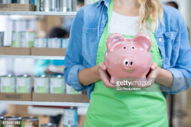Young female food bank volunteer holds piggy bank