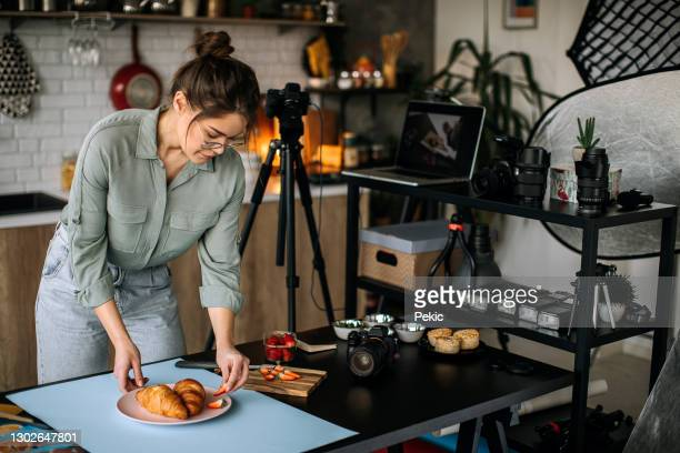 young female food photographer setting everything up for shooting - photographer stock pictures, royalty-free photos & images