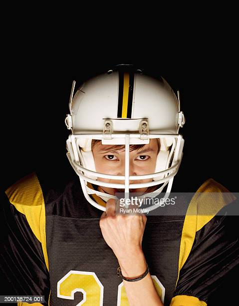 young female football player grasping helmet guard, portrait - guard american football player stock photos and pictures
