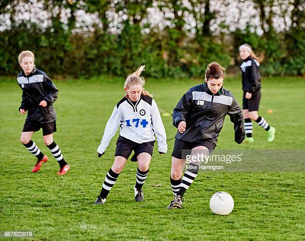 Young female footballer about to tackle opponent