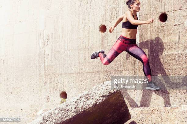 Young female free runner jumping across sea wall