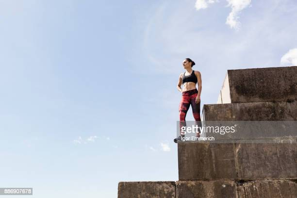 Young female free runner looking out from top of sea wall