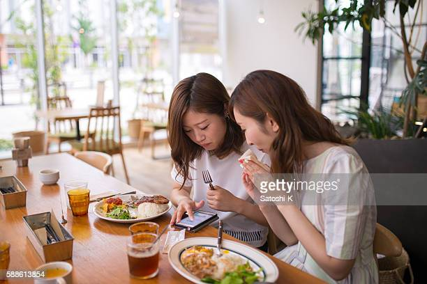 Young female friends checking SNS on smart phone at cafeteria