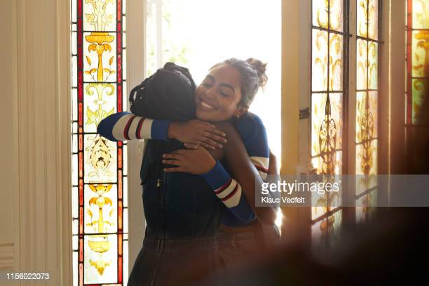 young female friends embracing at entrance - embracing stock pictures, royalty-free photos & images
