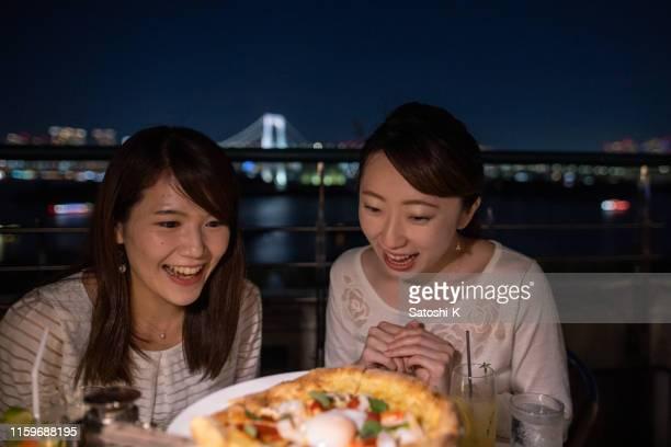 東京湾のオープンカフェでディナーを楽しむ若い女性の友達 - evening meal ストックフォトと画像