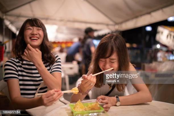 young female friends enjoying in night festival - street food stock pictures, royalty-free photos & images