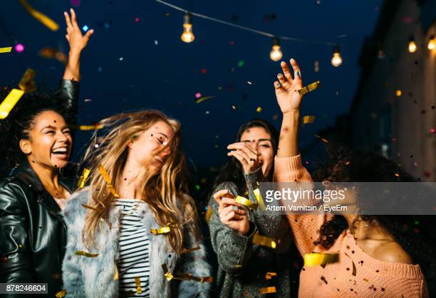 young female friends enjoying party at night - party stockfoto's en -beelden
