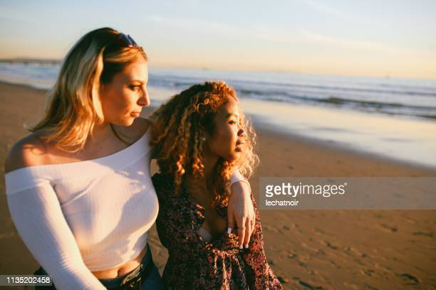 young female friends enjoying the walk on the venice beach in la, california - horizon over water stock pictures, royalty-free photos & images