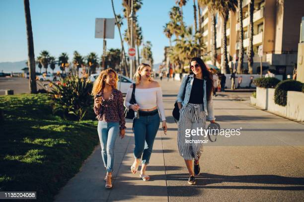 young female friends enjoying the walk on the venice beach in la, california - venice beach stock pictures, royalty-free photos & images