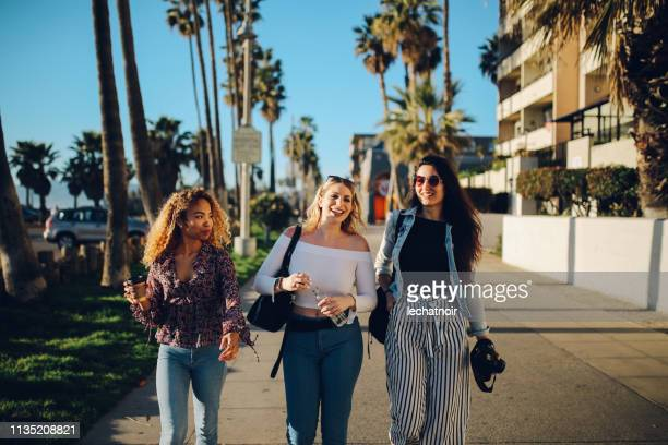 young female friends enjoying the walk on the venice beach in la, california - venice foto e immagini stock