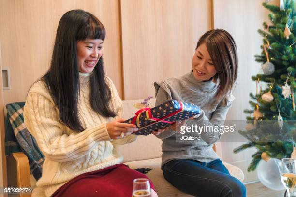 Young female friends exchanging Christmas presents