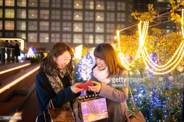 young female friends exchanging gifts on christmas - national holiday stock photos and pictures