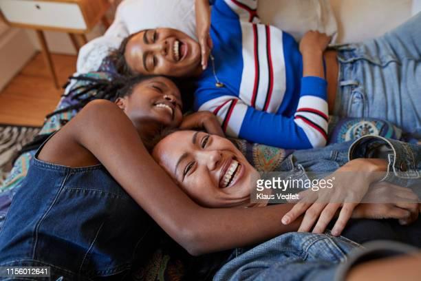 young female friends lying on bed at home - três pessoas - fotografias e filmes do acervo
