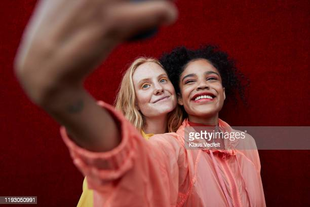 young female friends photographing outdoors - female friendship stock pictures, royalty-free photos & images