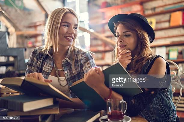 Jovens femininos amigos, preparar os seus exames na biblioteca.