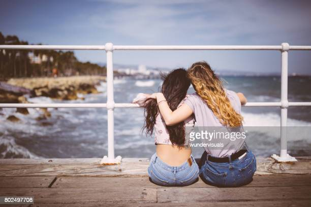 Junge Freundinnen sitzen auf der Mole mit Blick auf das Meer