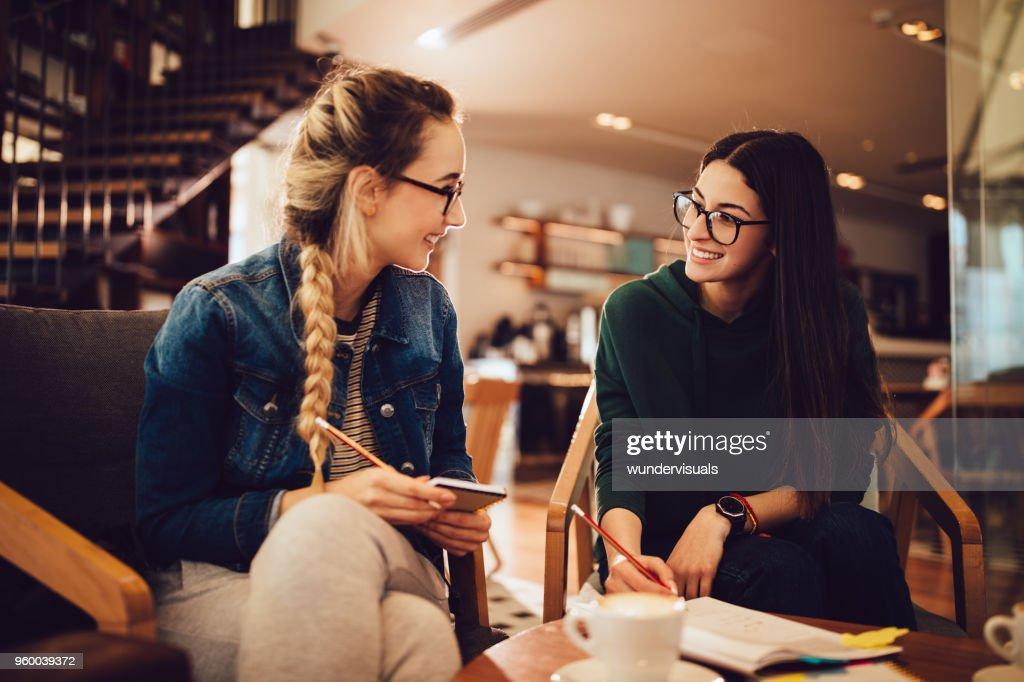 Junge Freundinnen, die gemeinsam für die Schule im Café studieren : Stock-Foto