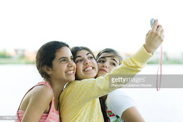 Young female friends taking photo of selves with cell phone