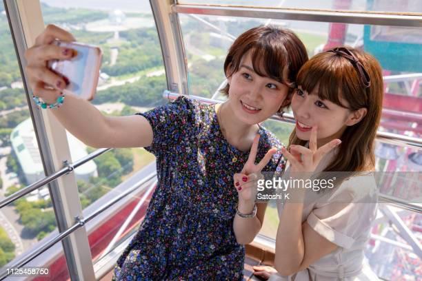 観覧車の selfie 写真を撮る若い女性の友人 - 女子大生 ストックフォトと画像