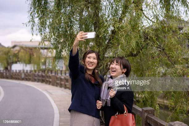 古い村の柳の木の下で自分撮り写真を撮る若い女性の友人 - 千葉県 ストックフォトと画像