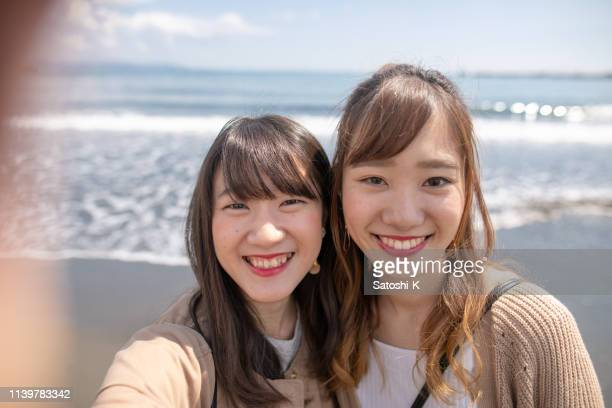 young female friends taking selfie pictures in front of pacific ocean - self portrait photography stock pictures, royalty-free photos & images