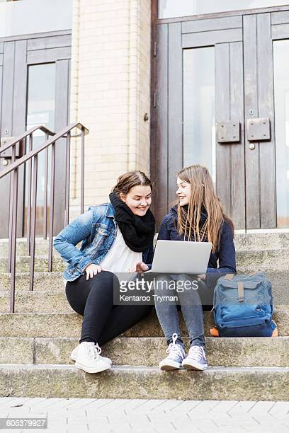 Young female friends using laptop on steps outside school building