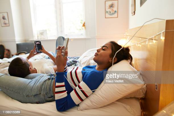 young female friends using mobile phones in bedroom - facebook friends stock pictures, royalty-free photos & images