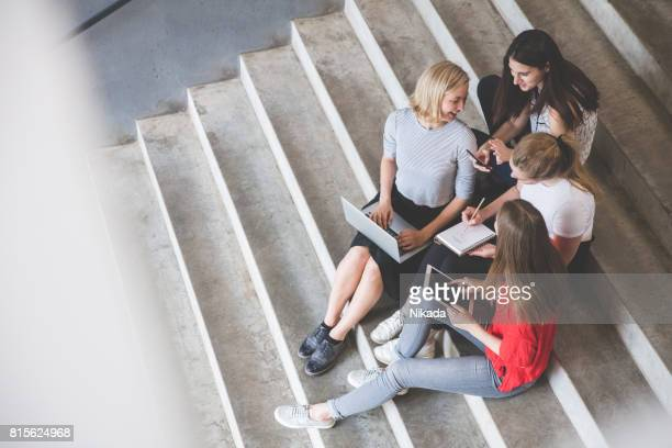 Young female friends using technologies while sitting on steps outdoors