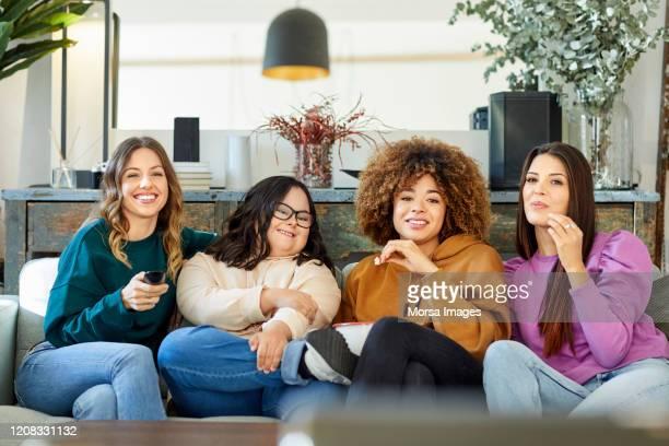 giovani amiche che guardano la tv a casa - disabilitycollection foto e immagini stock