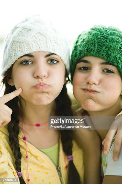 Young female friends wearing knit hats, puffing out cheeks