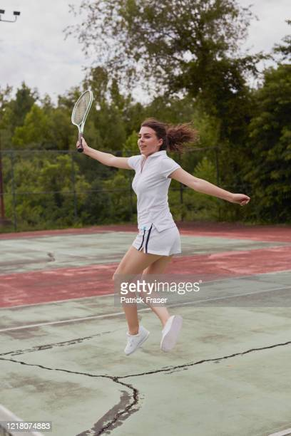 young female full length jump on hard green and red tennis court - racquet stock pictures, royalty-free photos & images