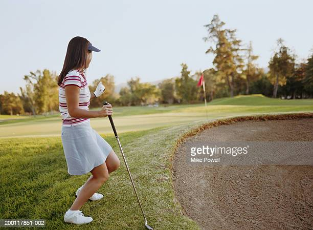 young female golfer celebrating on course, flag in background - バンカー ストックフォトと画像