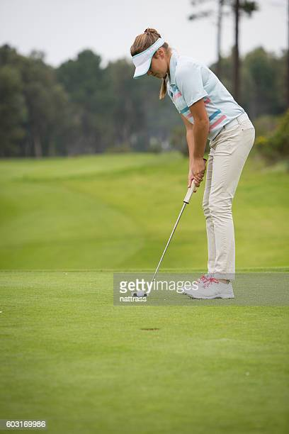 young female golfer hits a great putt - putting stock pictures, royalty-free photos & images