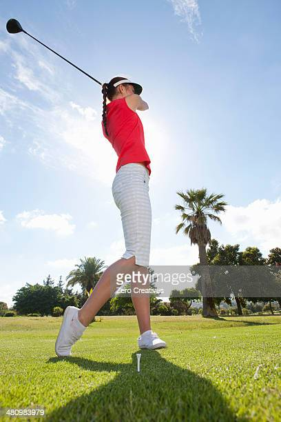 Young female golfer practicing golf swing